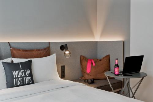 A bed or beds in a room at Moxy Frankfurt City Center