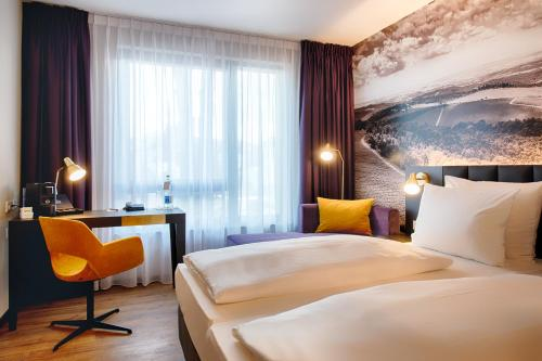 A bed or beds in a room at Welcome Hotel Neckarsulm