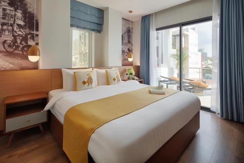 A bed or beds in a room at Little Saigon Boutique Hotel
