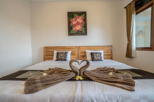 A bed or beds in a room at Baba Homestay