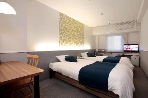 A bed or beds in a room at Hotel Plaza Osaka