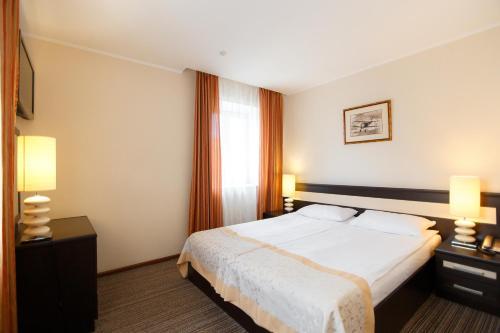 A bed or beds in a room at Reikartz Kropivnytskiy Hotel