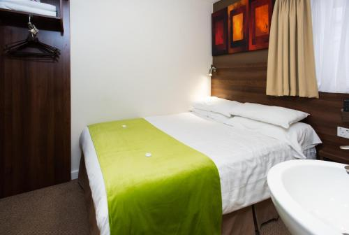 A bed or beds in a room at Marble Arch Inn