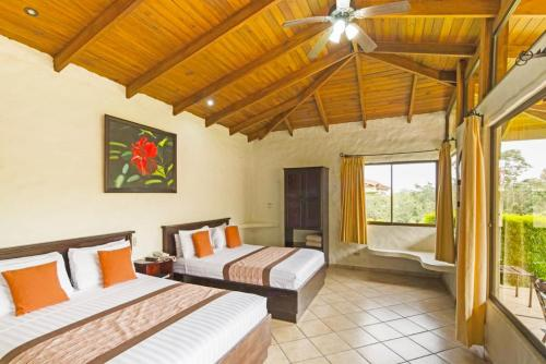 A bed or beds in a room at Arenal Volcano Inn