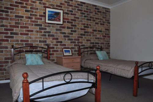A bed or beds in a room at 23 Carlo Road - Lowset family home within walking distance to the shopping centre. Pet friendly
