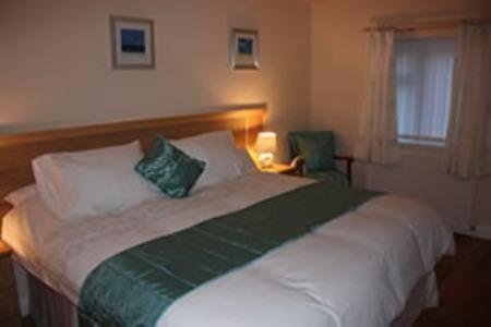 A bed or beds in a room at The Anvil Lodge