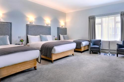 A bed or beds in a room at Sandymount Hotel