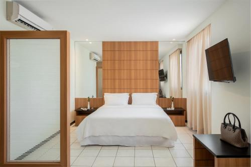 A bed or beds in a room at Intercity Cuiabá
