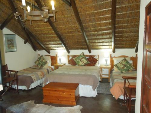 A bed or beds in a room at Trees Too Guest Lodge