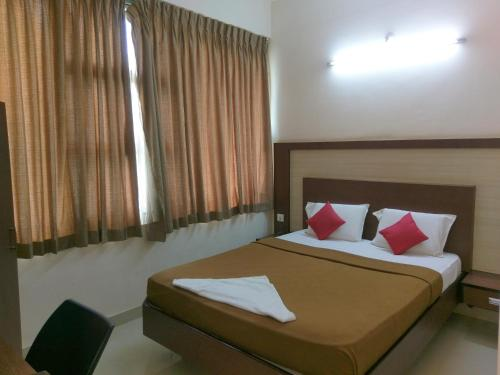 A bed or beds in a room at Banyan Tree Comforts Mysore