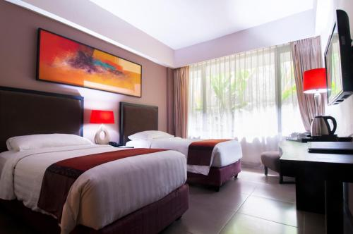 A bed or beds in a room at 100 Sunset Kuta Hotel & Ballroom
