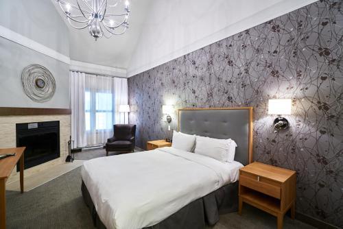A bed or beds in a room at Hotel Chateau Bromont