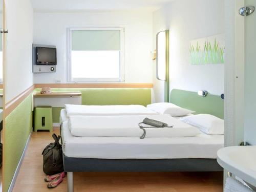 A bed or beds in a room at ibis budget Dortmund West