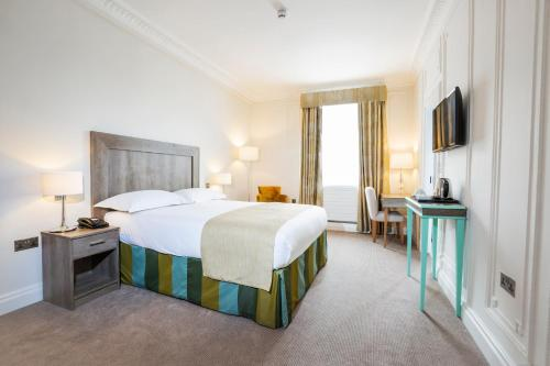 A bed or beds in a room at Astor Court Hotel