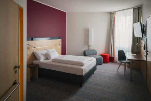 A bed or beds in a room at Vienna House Easy Bratislava