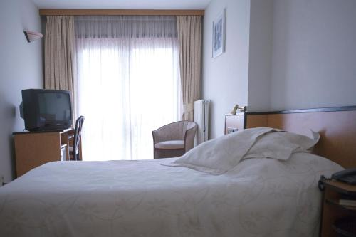 A bed or beds in a room at Hotel Des Zouaves