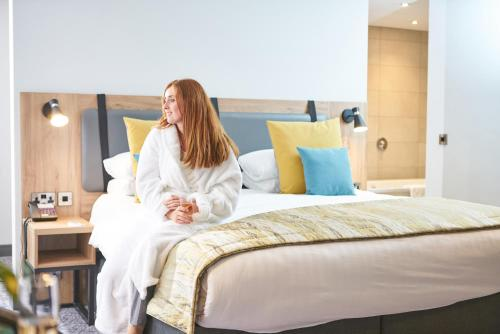 A bed or beds in a room at Mercure Newcastle George Washington Hotel Golf & Spa