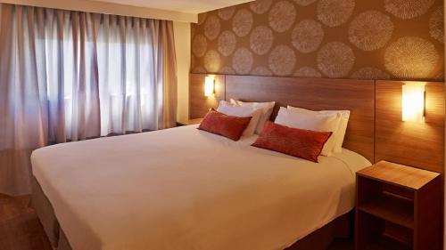 A bed or beds in a room at Mercure Curitiba 7 de Setembro