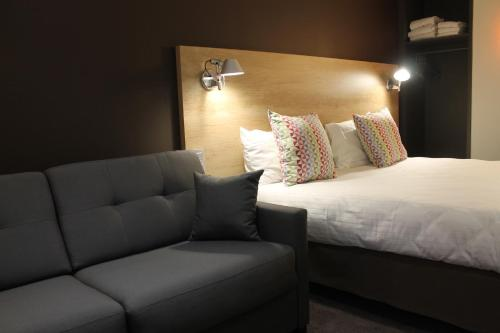 A bed or beds in a room at Campanile Laval Nord