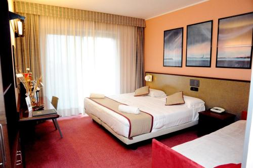 A bed or beds in a room at Gotha Hotel Turin Airport