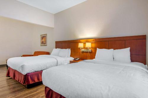 A bed or beds in a room at Clarion Suites Duluth I-85