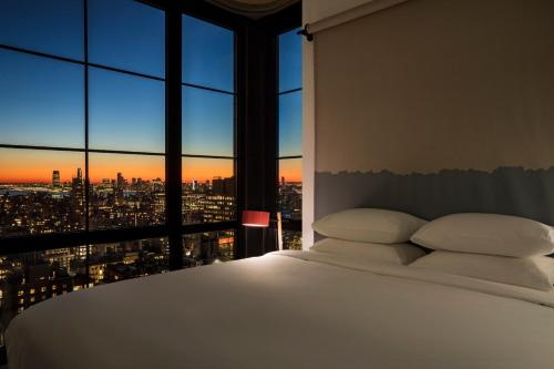 A bed or beds in a room at Moxy NYC Chelsea