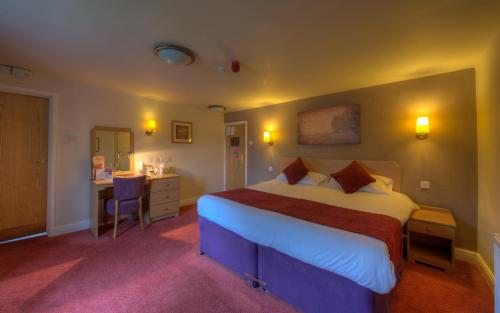 A bed or beds in a room at Rockingham Arms By Greene King Inns