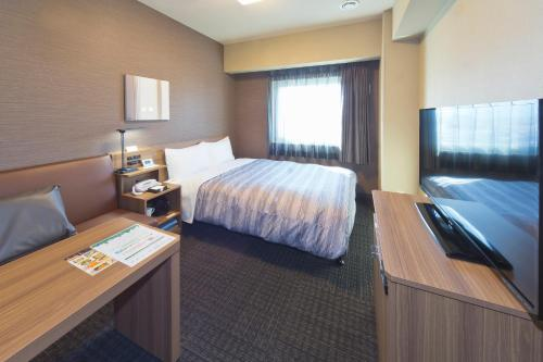A bed or beds in a room at Hotel Route-inn Yamaguchi Yuda Onsen