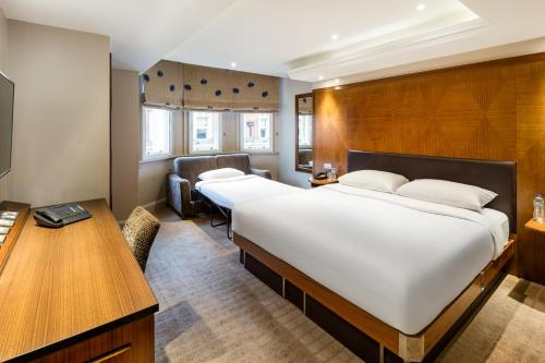 A bed or beds in a room at Radisson Blu Edwardian Kenilworth Hotel, London