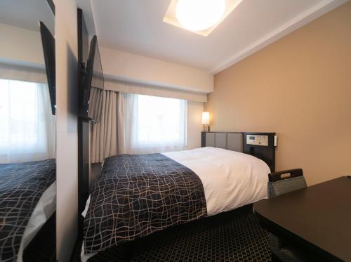 A bed or beds in a room at APA Hotel Shin-Osaka-Ekiminami