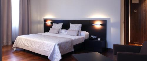 A bed or beds in a room at Hotel Palacio de Merás