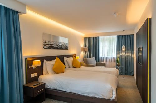 A bed or beds in a room at Pelican London Hotel and Residence