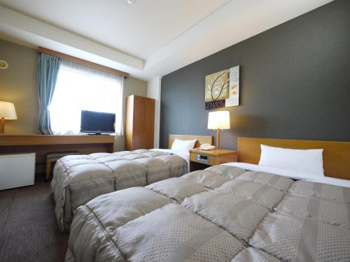 A bed or beds in a room at Hotel Route-Inn Court Fujioka