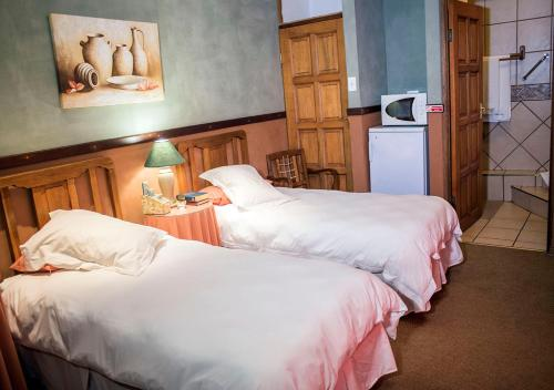A bed or beds in a room at Kleine Eden Guesthouse