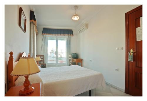 A bed or beds in a room at Hostal La Posada