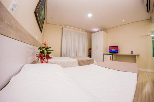 A bed or beds in a room at Hotel Recanto Do Rouxinol