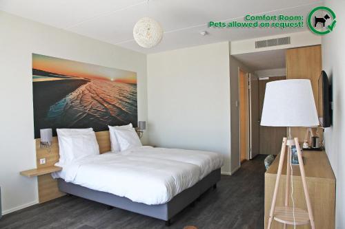 Een bed of bedden in een kamer bij Strandhotel Duinoord