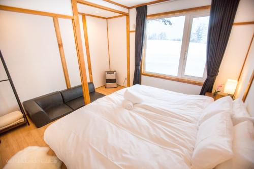 A bed or beds in a room at RUSUTSU HOLIDAY CHALET