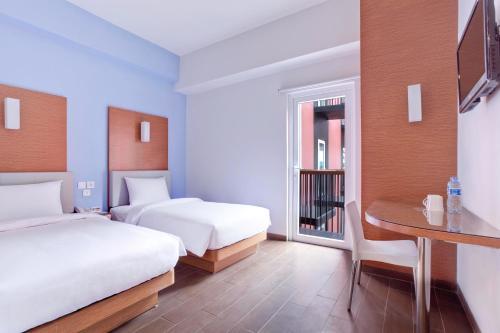A bed or beds in a room at Amaris Hotel Pratama Nusa Dua