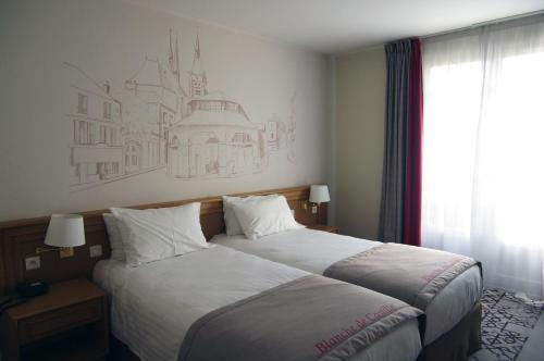 A bed or beds in a room at Best Western Blanche de Castille Dourdan