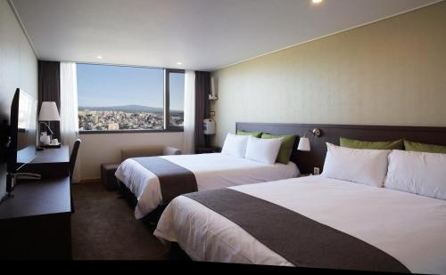 A bed or beds in a room at Hotel Shalom Jeju