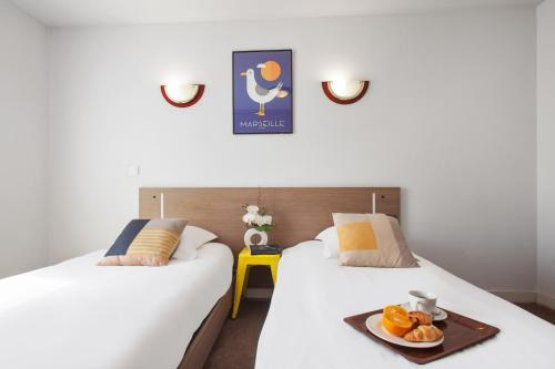 A bed or beds in a room at Appart'City Marseille Euromed