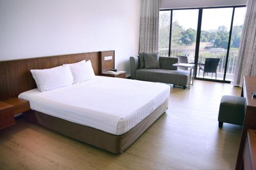 A bed or beds in a room at The Bayview Beach Resort