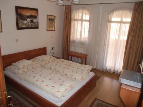 A bed or beds in a room at Sóvirág Vendégház