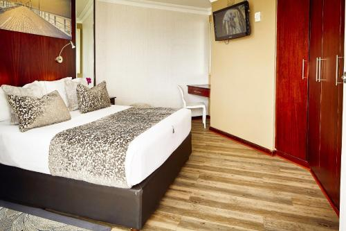 A bed or beds in a room at First Group The Palace All-Suite