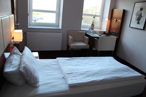 A bed or beds in a room at Adena Hotel