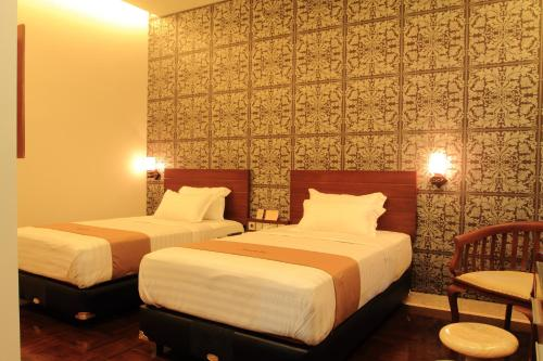 A bed or beds in a room at Omah Qu Guesthouse Malioboro