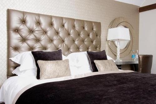 A bed or beds in a room at Sanctum On The Green-A Luxury Hotel