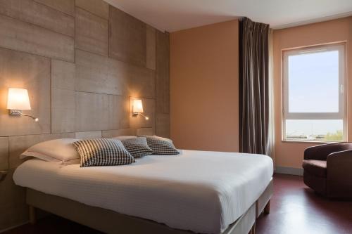 A bed or beds in a room at The Originals Boutique, Hôtel Alizé, Évian-les-Bains (Inter-Hotel)