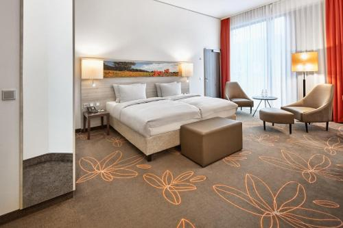 A bed or beds in a room at H4 Hotel Münster